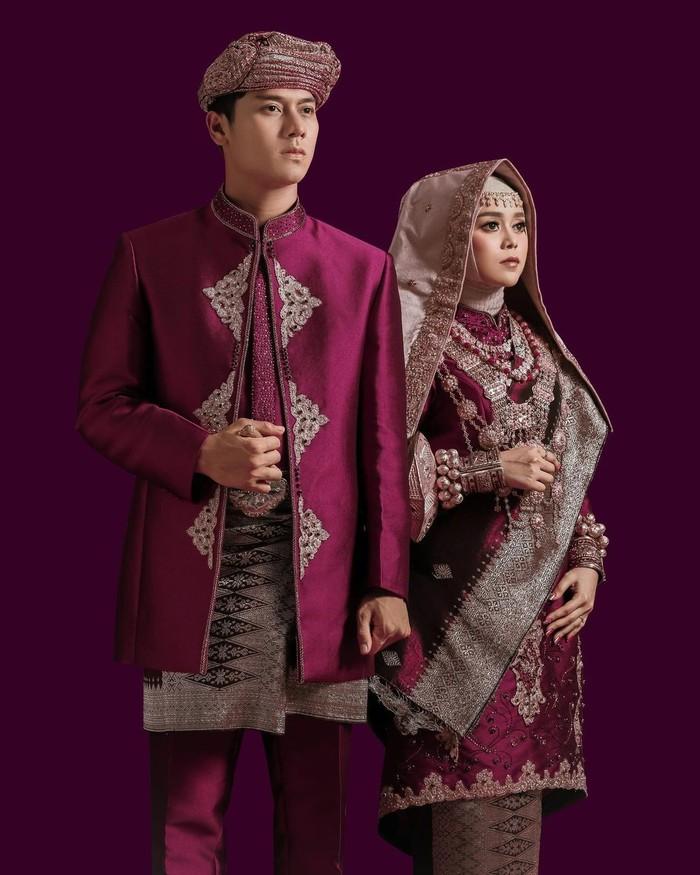 Lesti terlihat sangat anggun dengan pakaian minang nuansa ungu yang dipadukan dengan tengkuluk talakuang berwarna emas. Begitu pula dengan Billar yang nampak memesona dengan jas nuansa ungu dan kain songket yang senada. (Foto: Instagram.com/aldiphoto)