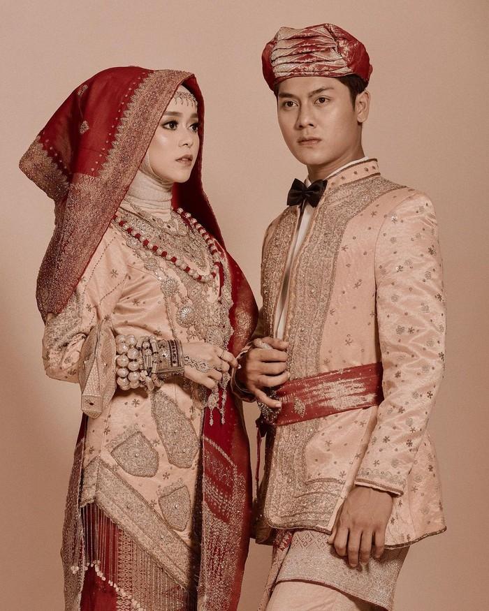 Masih dalam balutan pakaian adat minangkabau, mereka mengenakan pakaian warna serasi dengan perpaduan kain songket merah hati. Tambahan dasi kupu-kupu hitam yang dikenakan Rizky Billar membuatnya semakin terlihat menawan. (Foto: Instagram.com/aldiphoto)