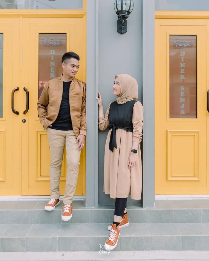 Apakah pasanganmu adalah tetanggamu juga? Mungkin ide pose foto ini bisa jadi menari untuk menggambarkan kisahmu. Bersandar di tembok dan saling berpandangan ini membuat fotomu seolah berbicara. (Foto: instagram.com/preweddingkeren/)