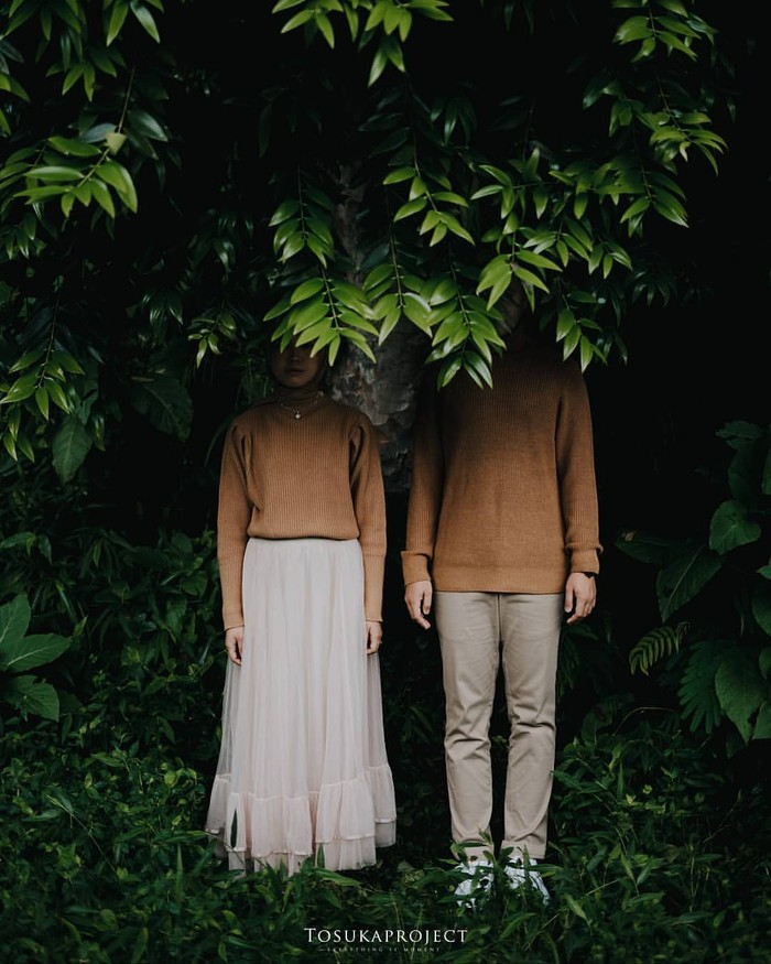Kamu bisa menampilkan adegan bersembunyi di balik dedaunan di bawah pohon lebat. Bagian wajah yang tertutup memberikan kesan misterius. (Foto: instagram.com/preweddingkeren/)