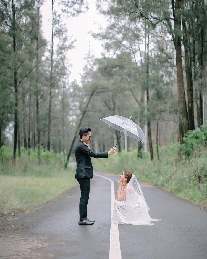 Kamu dan pasanganmu bisa menggunakan berbagai properti foto seperti payung, kacamata, dan lainnya. Lalu buatlah berbagai adegan yang unik atau mengisahkan perjalanan hubunganmu. (Foto: instagram.com/preweddingkeren/)