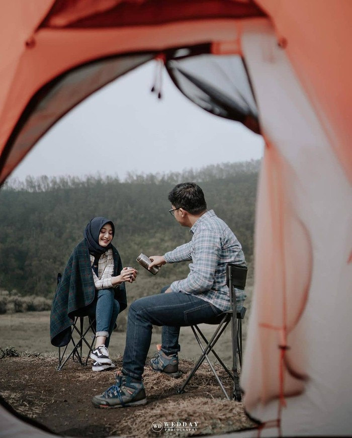 Pasangan pecinta alam wajib banget sih punya foto pre wedding di gunung, danau, hutan atau tempat lainnya. Sudut pandang dari tenda serta adegan menuangkan minuman ini terlihat sangat menarik. (Foto: instagram.com/preweddingkeren/)