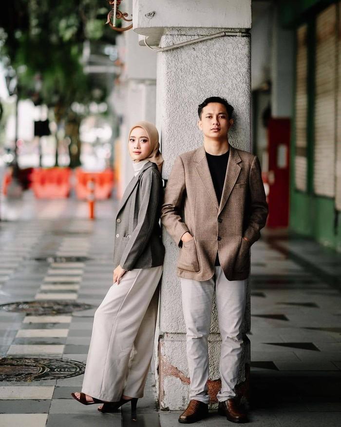Pose foto menggunakan jas dan blazer ini cocok untuk kamu yang bertemu dengan pasangan di kantor. Pose foto saling menyandarkan diri di tiang ini terlihat elegan dan effortless. (Foto: instagram.com/preweddingkeren/)