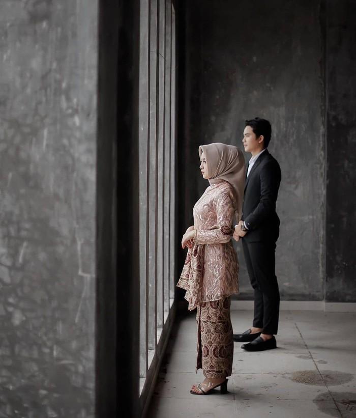 Potret menatap masa depan ini juga bisa jadi ide pose foto pranikah tidak bersentuhan. Kamu dan pasangan bisa mengenakan setelan jas serta kebaya untuk kesan yang formal. Foto ini terkesan serius dan elegan. (Foto: instagram.com/preweddingkeren/)