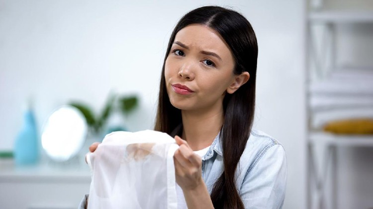 Upset asian housewife showing coffee stain on shirt at camera, laundry service