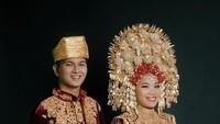 <p>Mumuk dan Eno mengenakan busana pengantin khas Minang yang biasa disebut dengan busana anak daro. Tak sedikit pula yang awalnya pangling, mengira foto Mumuk dan Eno sebagai pasangan Lesti dan Billar. Diketahui bahwa pasangan Leslar juga memakai baju adat minang serupa ya, Bunda. (Foto: Instagram @enoretra)</p>