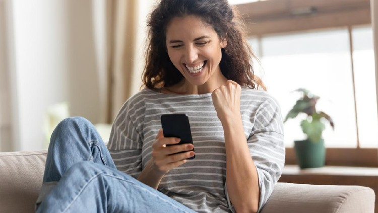 Overjoyed young pretty woman making yes gesture, reading unbelievable news on smartphone. Excited millennial attractive lady looking at mobile screen, receive online lottery win notification.