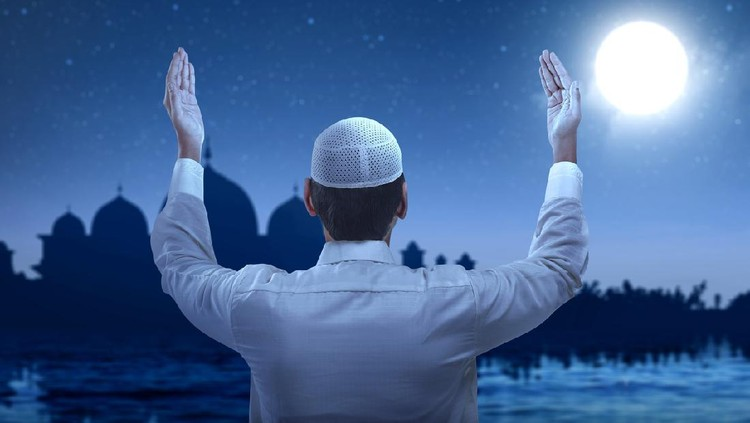 Rear view of Asian Muslim man standing while raised hands and praying with the night scene background