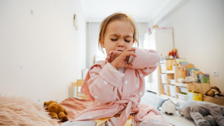 Sick 3 years old girl coughing in bed