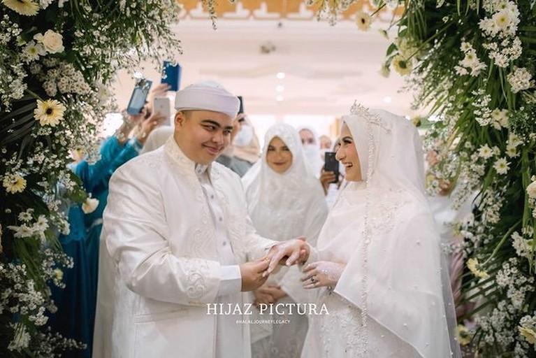 Putra bungsu Alm Ustaz Arifin Ilham, Ameer Azzikra telah resmi menikahi Nadzira Shafa. Yuk kita intip momen bahagia mereka!