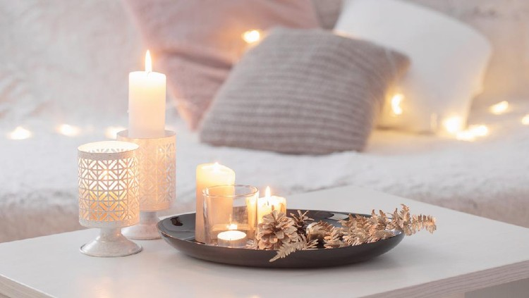Christmas decoration   with burning candles on  white table against the background of  sofa with plaids and pillows. Cozy home and holiday concept