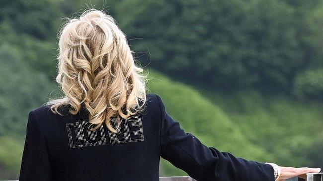Jill Biden menggunakan blazer hitam dengan tambahan beads bertuliskan 'LOVE.' Tulisan ini dikaitkan juga dengan kasus jaket 'I Really Don't Care' Melania Trump.