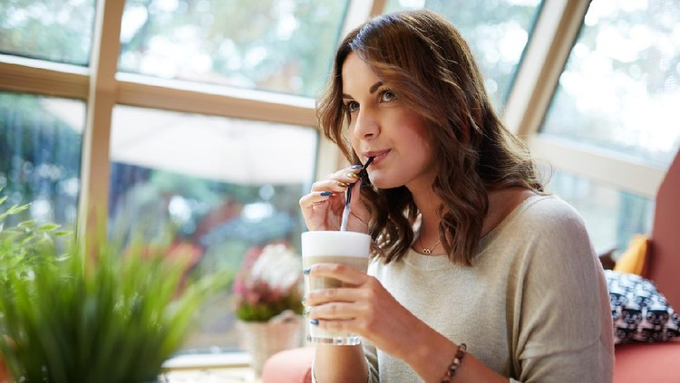 Portrait of young beautiful woman relaxing at cafe drinking coffee.