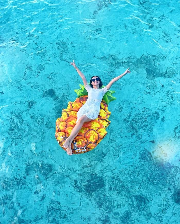 Saat honeymoonnya kemarin, Nanda membagikan potretnya yang tengah berjemur dengan float ban berbentuk nanas. Pemandangan jernih air laut terlihat kontras dengan float ban yang digunakan. (Instagram.com/nandaarsynt)