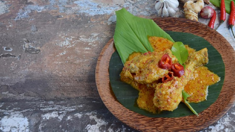 Ayam Kalio Padang or wet saucy chicken rendang. Served on banana leaf and turmeric leaf garnish with chili and kaffir lime leaf