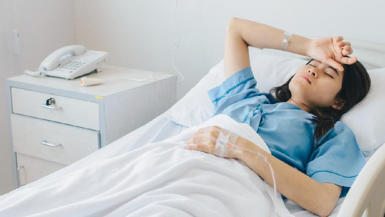 Asian female patient warded and laying on the bed connected to multiple medical devices