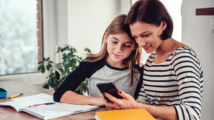 Mother using smart phone and helping daughter with homework at the table in dining room by the window