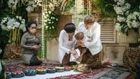 <p>Titi dan keluarga kompak mengenakan pakaian adat Jawa warna putih dengan kain batik cokelat, nih. Sementara itu, sang suami dan Bhaskara mengenakan blangkon dengan warna senada. Kehadiran sang suami pun curi perhatian netizen. (Foto: Instagram: @titiradjopadmaja)</p>