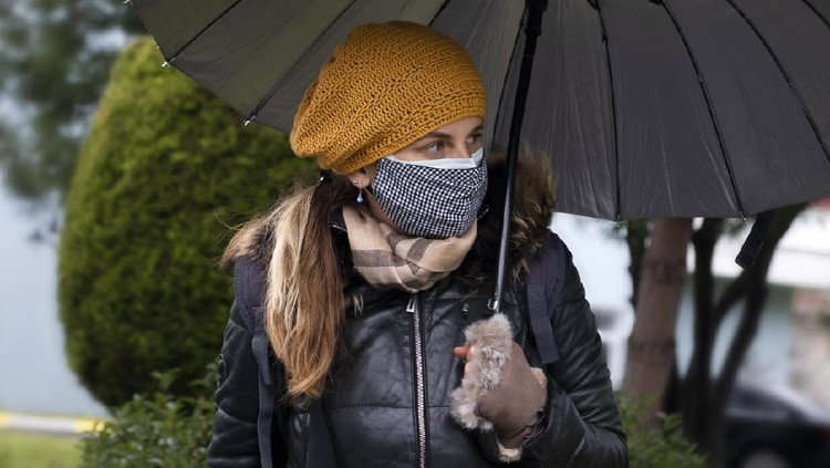 Close up of a beautiful woman with double medical masks in the outdoors. Mid adult standing in front of her house and waiting for friend or taxi.