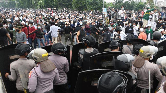 Bentrok polisi dan massa pendukung Rizieq, menurut Kapolres Metro Jakarta Timur Kombes Erwin Kurniawan, dipicu ulah massa yang menceburkan kendaraan ke sungai.