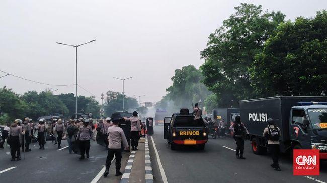 Massa pendukung Rizieq berlarian masuk ke perkampungan sekitar PN Jakarta Timur usai polisi menembakkan gas air mata dan meminta massa bubar.