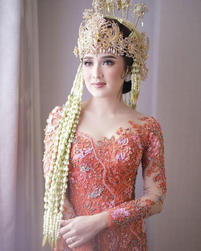 Berbeda dengan pengantin kebanyakan yang memilih putih, Rosiana Dewi memilih memadupadankan Siger Sunda berwarna gold dengan kebaya berwarna oranye di hari akadnya. Dengan padanan ini, Rosiana tampil sangat fresh! (Instagram/rsn.dw)