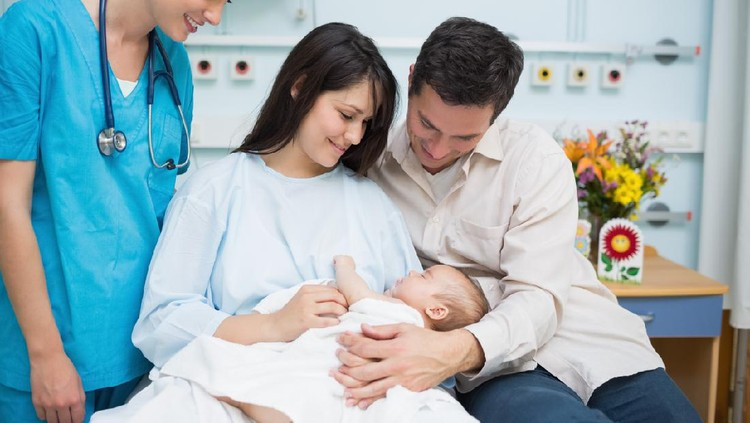 Father and mother holding a new born baby with a doctor in a hospital room