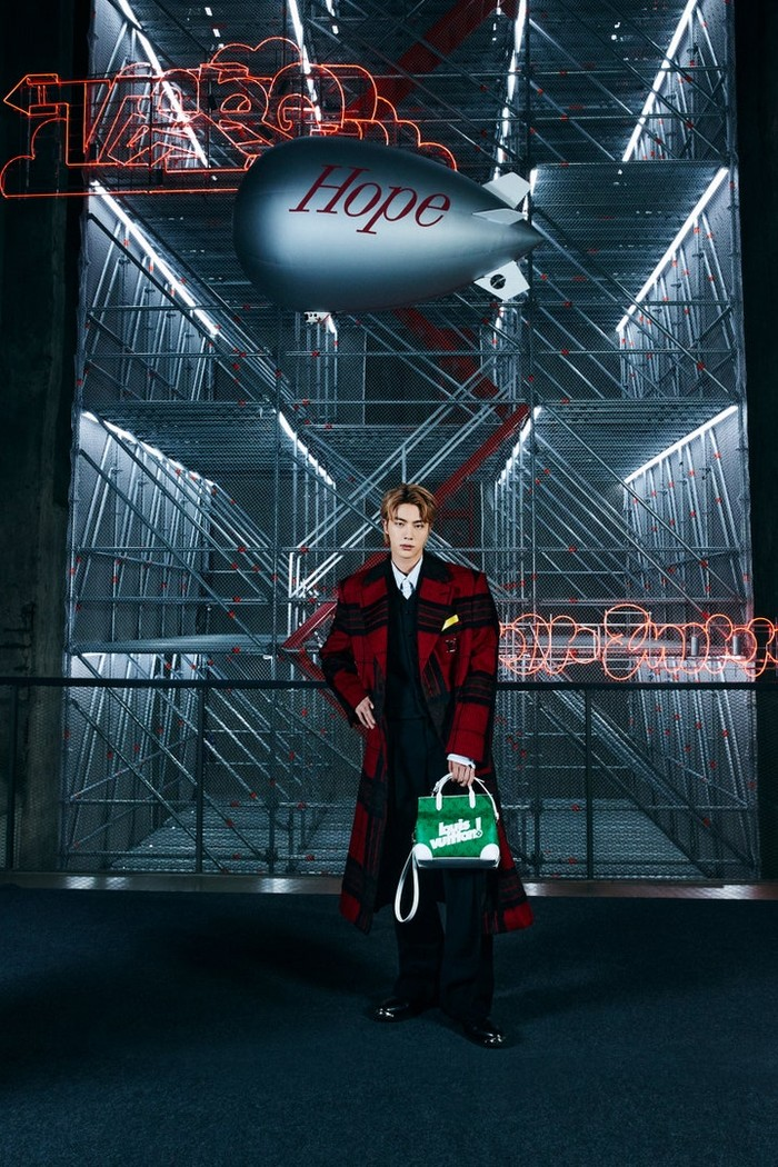 Dengan nuansa hitam merah, Jin tampak sangat elegan memegang tas berwarna hijau. /Photos: Courtesy of Louis Vuitton/Instagram @voguejapan