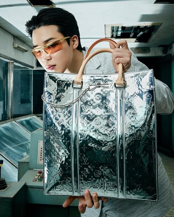 Jimin tampil nyentrik dalam balutan setelan berwarna abu-abu dan kacamata berbingkai emas. Ia memperlihatkan tote bag silver dengan detail logo Louis Vuitton. (Foto: Instagram.com/louisvuitton)