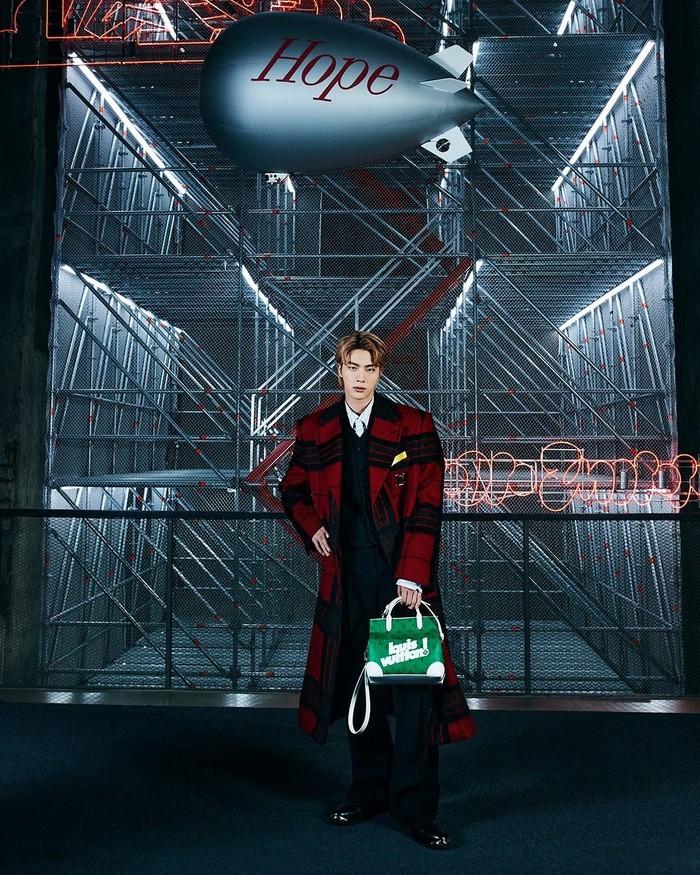 Jin tampak memukau dibalut mantel dengan perpaduan warna merah dan hitam. Ia juga membawa tas jinjing yang warnanya kontras dengan mantel yang dipakainya. (Foto: Instagram.com/louisvuitton)