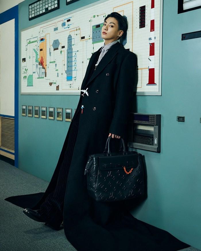 Jungkook tampil serba hitam dengan setelan jas dan tas jinjing yang diperlihatkannya. Jas yang ia pakai cukup unik karena panjangnya hingga 'menyapu' lantai. (Foto: Instagram.com/louisvuitton)
