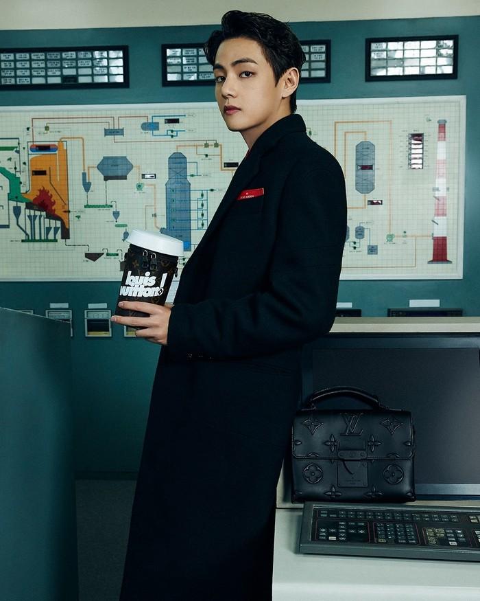 V tampil menggunakan jas panjang berwarna hitam yang dipadukan dengan kemeja berwarna merah. Ia juga menampilkan tas jinjing hitam yang dihiasi logo Louis Vuitton. (Foto: Instagram.com/louisvuitton)