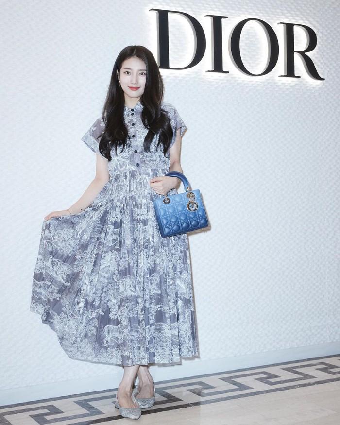 Di kesempatan ini, Suzy hadir mengenakan pakaian lengkap bermerek Dior. Mulai dari Dioriviera Mid-Length Dress, Lady Dior My ABCDior Bag, flat shoes J'adior Slingback Ballerina, serta aksesoris gelang dan anting dari Dior. (Foto: Instagram.com/voguekorea)