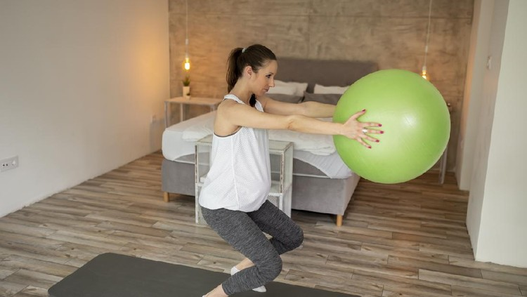 Pregnant woman exercising at home during the third trimester practicing healthy and active lifestyle during pregnancy