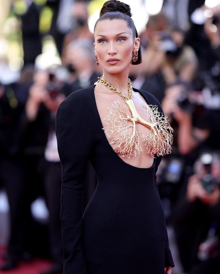Bella Hadid mengenakan gaun lengan panjang berbahan wool crepe dengan kerah berpotongan rendah,ditambah kalung kuningan berlapis emas berbentuk paru-paru./Foto: instagram.com/schiaparelli