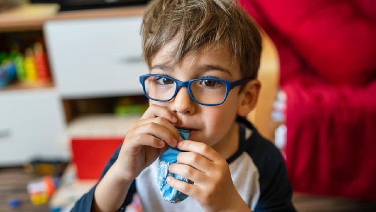 Portrait of happy caucasian boy with eyeglasses sitting at home in room in day real people small male playful child playing on the floor inflating balloon