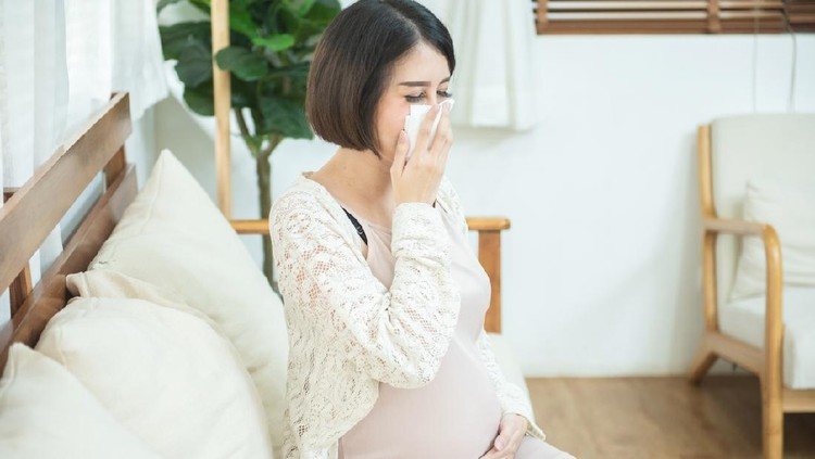 pregnant asian female use tissue paper close mouth and nose, she cough and feeling fever, pregnancy and people concept - sick pregnant woman blowing nose with paper tissue at home