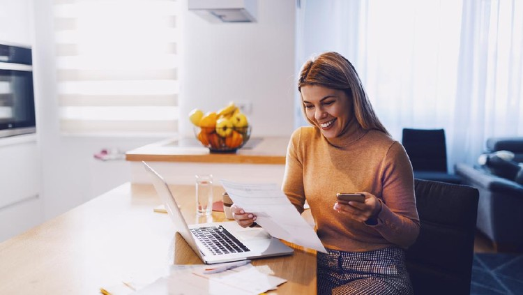 Cute caucasian smiling blonde woman in sweater holding bills in one hand and in other smart phone. On table are laptop and bills. Apartment interior.