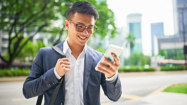 Young malaysian businessman in the streets of downtown Kuala Lumpur smiling while looking to his his smart phone for a crowed sourced taxi to arrive . Kuala Lumpur, Malaysia, Asia