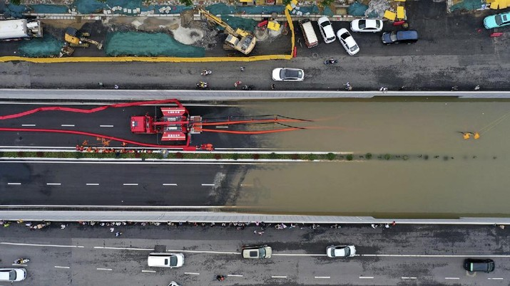 In this aerial photo released by Xinhua News Agency, firefighters pump rainwater from a road underpass in Zhengzhou in central China's Henan province on Wednesday, July 21, 2021. China's military has blasted a dam to release floodwaters threatening one of its most heavily populated provinces, as the death toll in widespread flooding rose to more than two dozens. (Ma Xiaoran/Xinhua via AP)
