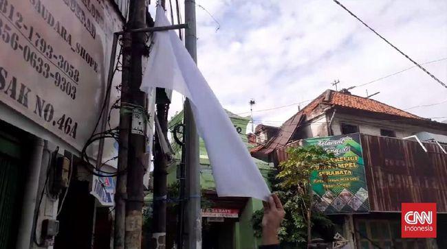 Pengibaran bendera merah putih menyimbolkan kondisi menyerah karena masalah ekonomi imbas dari kebijakan PPKM tanpa bantuan keuangan dari pemerintah.