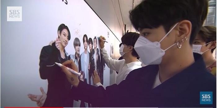 Masing-masing member menandatangi poster foto mereka yang terpampang di lobby. (foto:youtube/SBSnews)