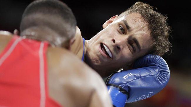 Petinju Maroko Youness Baalla mencoba menggigit petinju Selandia Baru David Nyika dalam pertarungan tinju kelas berat di Olimpiade Tokyo 2020.