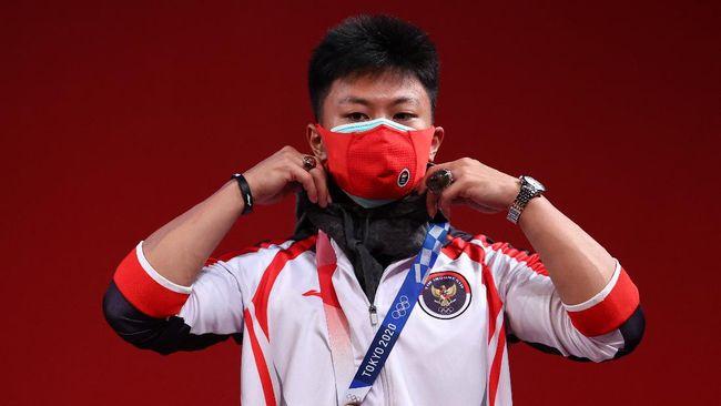 Rahmat Erwin Abdullah mempersembahkan medali ketiga bagi Indonesia di Olimpiade Tokyo dengan kondisi cedera paha jelang melakukan angkatan clean & jerk.