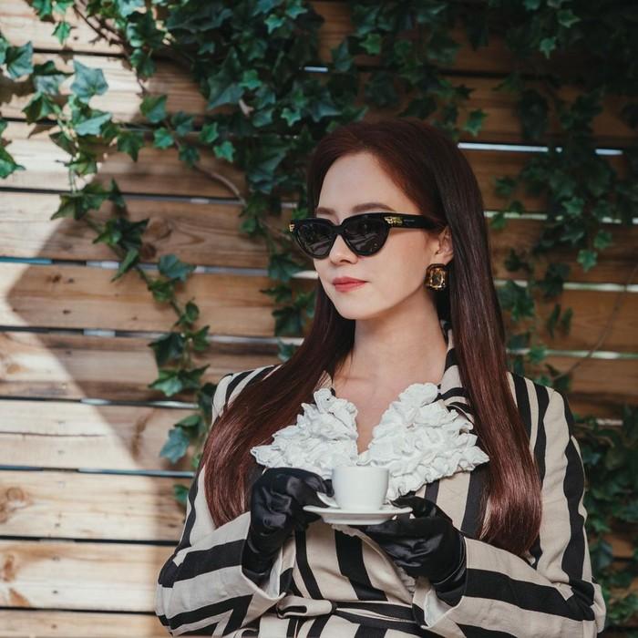 Kali ini Song Ji Hyo memiliki tampilan yang mewah seperti seorang bangsawan yang sedang menikmati kopinya. Dress dengan motif stripe dengan aksen ruffle pada bagian kerah memberi kesan manis, meski tampilannya badass. /Foto: instagram.com/tving.official
