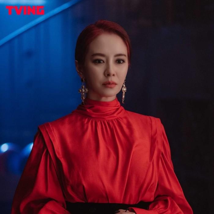 Nggak cuma warna hitam, Song Ji Hyo juga tampil badass dengan gaun berwarna merah senada dengan rambutnya. Anting panjang yang dipakainya tampak mewah dan stand out./Foto: instagram.com/tving.official