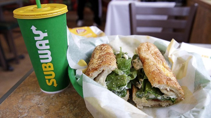 The Subway logo is seen on on a soft drink cup next to a sandwich at a restaurant in Londonderry, N.H., Friday, Feb. 23, 2018. Subway is shaking up its loyalty rewards program, giving customers the ability to earn $2 discounts instead of free Footlongs. (AP Photo/Charles Krupa)