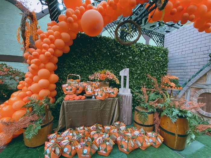 Buah orange, balon orange, hingga bunga-bunga berwarna orange cerah terlihat menghiasi tempat perayaan. Tak usai di situ, hampers untuk dibagikan pun didominasi warna senada. (Foto: Instagram.com/senjadeco)