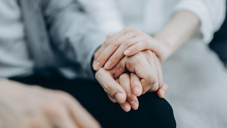 Cropped shot of a young couple sitting on sofa compassionately holding hands in self isolation during Covid-19 health crisis