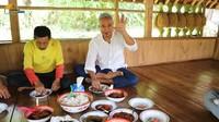 <p>Haji Usman Bimantara juga senang mengajak penduduk setempat untuk menikmati hidangan di gubuknya. Mereka menikmati makanan sederhana di tengah pemandangan sawah yang asri. (Foto: YouTube Petualangan Alam Desaku)</p>